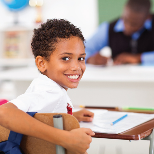 Young boy sitting in classroom, smiling at camera.
