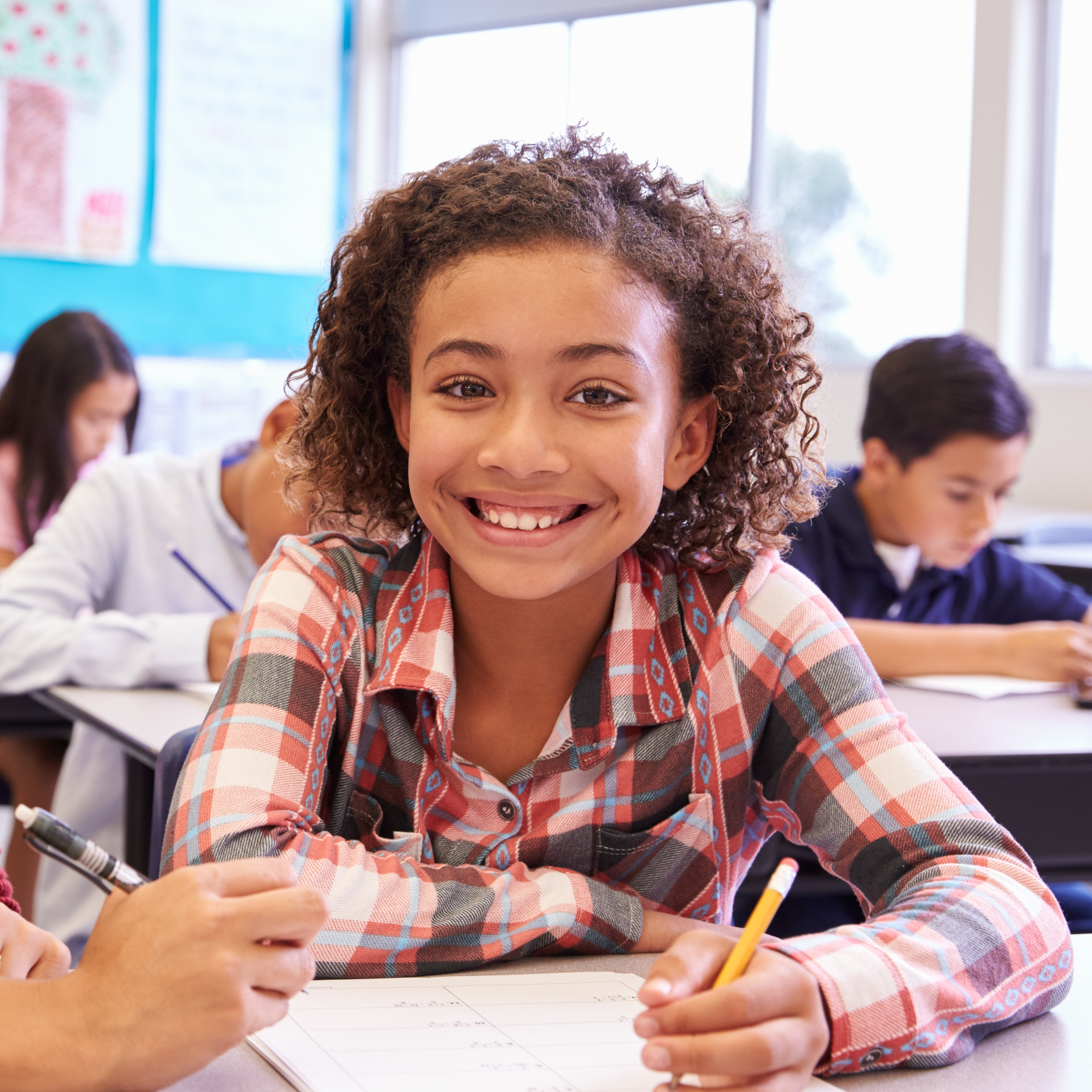 Smiling girl in a classroom setting holding a pencil and working on classwork